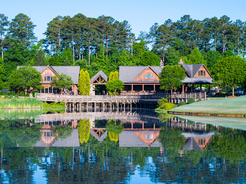 View of the clubhouse from across a pond at The River Club in Suwanee, Georgia